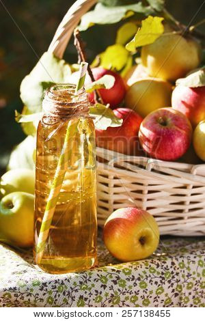 White Wicker Basket With Green And Red Apples, Apple Cider, Juice Or Vinegar In Glass Bottle, Leaves