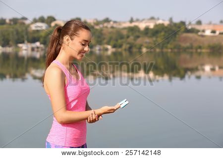 Young Woman Checking Pulse Outdoors On Sunny Day