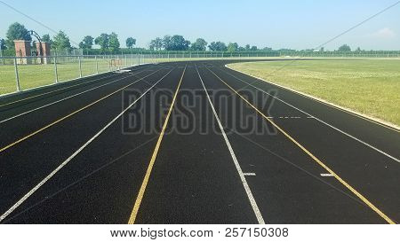 Eight Lane Black Asphalt Running Track In Stadium Black And White. Running Track On Blue Sky. Runnin