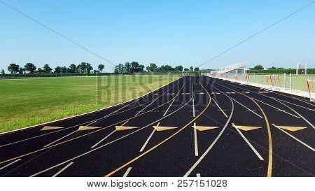 Eight Lane Black Asphalt Running Track In Stadium Black And White. Running Track On Blue Sky. Runnin