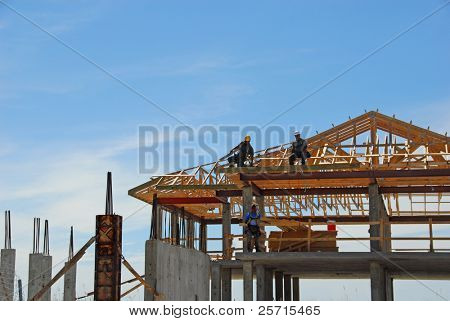 Elegant Beachfront Home Under Construction with Workers on Rafters