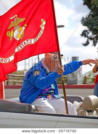 U.S. Military Veteran Holding Marine Corps Flag in Public Parade