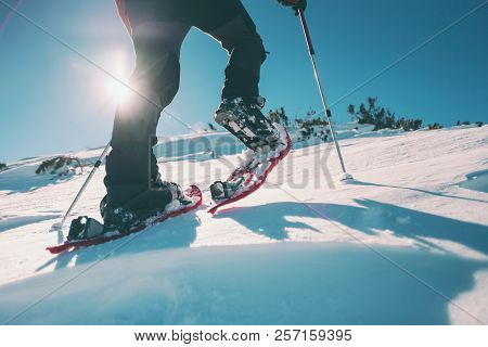 Man In Snowshoes In The Mountains.