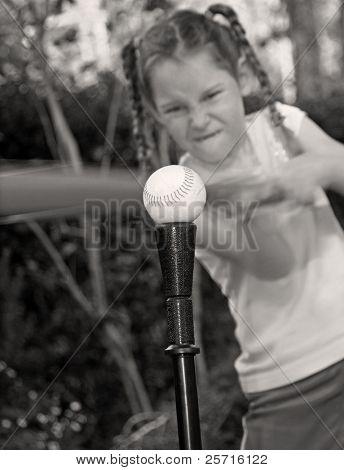 Young Tomboy Girl at Bat Hitting Ball
