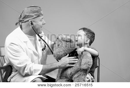 Family Physician Using Stethoscope on Young Boy's Bear