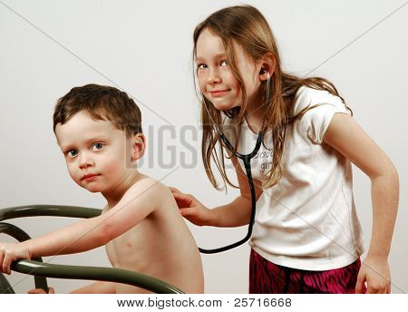 Young Girl Listening with Stethoscope to Young Boy