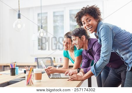 Laughing student with colleagues on laptop in successful business start-up