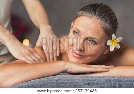 Senior woman in spa salon getting massage. Closeup of a beautiful woman during spa treatment. Beautiful mature woman receiving massage of shoulder at beauty salon.