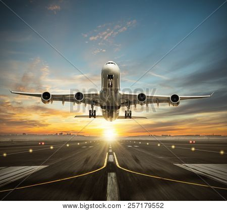 Huge two storeys commercial jetliner taking of runway. Modern and fastest mode of transportation. Dramatic sunset sky on background