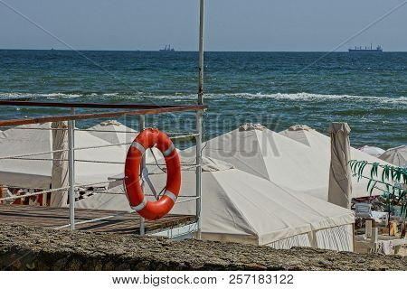 Red Lifebuoy On The Fence Of White Arbours Of Cloth On The Beach Near The Sea Waves