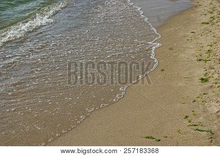 Sea Waves With White Foam On Sand With Seaweed