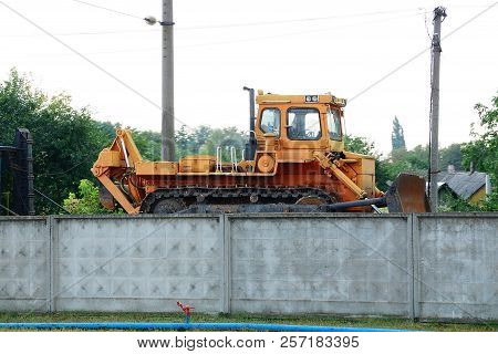 One Large Orange Tractor Stands At The Concrete Fence