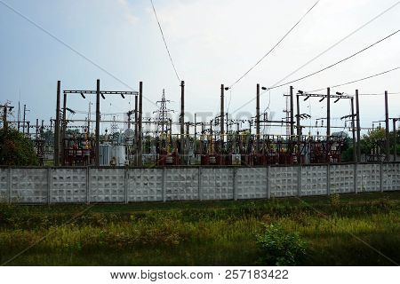 A Large Power Station Behind A Gray Fence Against The Sky