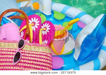 Pool toys and accessories on deck next to pretty pool water