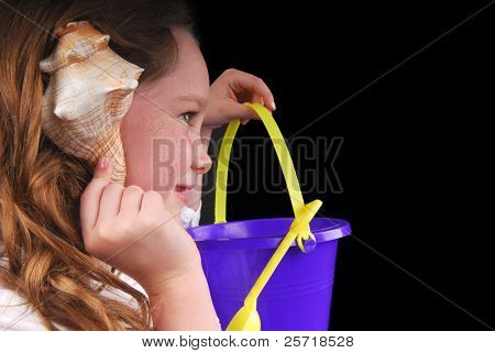 Young girl listening to seashell holding sand pail