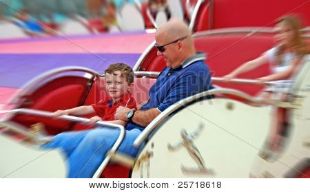 Father and children having fun on spinning amusement park ride