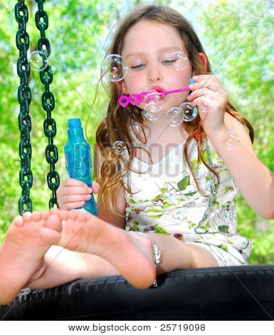 Young girl outside blowing bubbles while sitting on tire swing