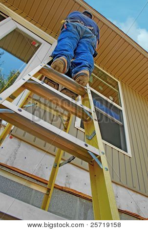 Construction worker high up on ladder