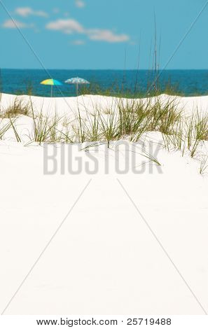 Pretty white sand dune with beach umbrellas by shore in distance