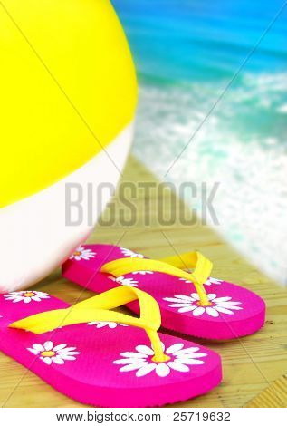 Colorful flipflop sandals and inflatable beach ball by ocean