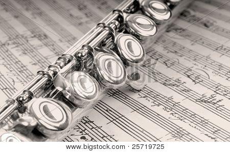 Silver flute instrument resting on handwritten music