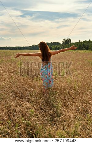 Young Woman Girl Standing With Her Back With Open Arms To The Sunset On A Wheat Field In The Country