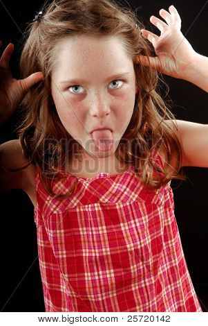 Young freckle faced girl making face by sticking out tongue