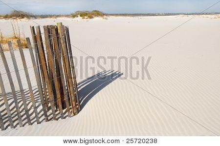Coiled sand dune fence on beach with rippled sand