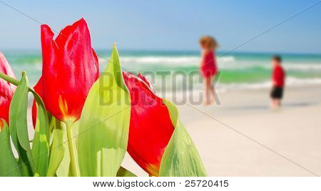 Tulips in foreground with young boy and girl playing happily at beach
