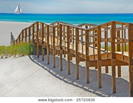 Wooden boardwalk leading to pretty beach with sailboat on horizon