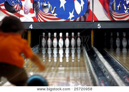 Young child rolling the ball at bowling alley