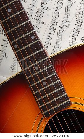 Neck of acoustic guitar resting on music