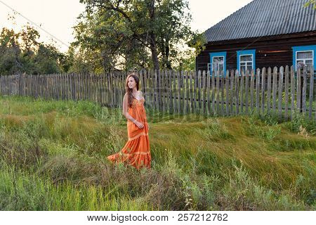 At The Late In The Evening A Young Woman In A Retro Village Attire Strolls Along The Old Stockade An