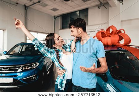 A Guy Shows A New Car To Girlfriend. Present Concept. Staring At Each Other. Automobile Salon. Make