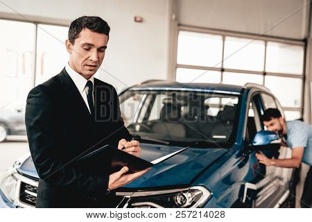 Car Dealer Camera Posing With A Buyer On Background. Cheerful Customer. Automobile Salon. Make A Dec