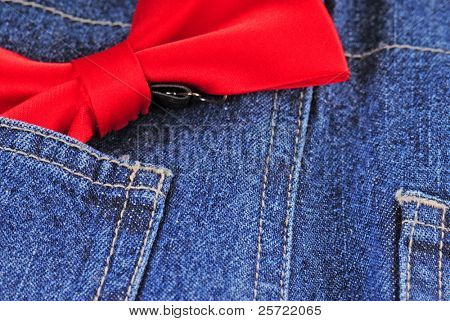 Red bow tie in pocket of blue jeans