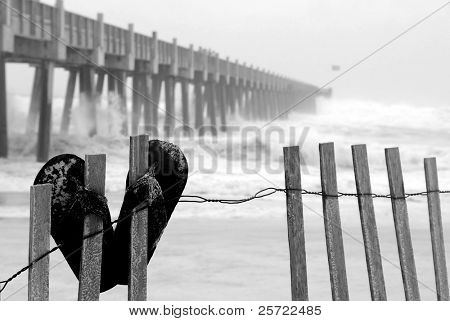 Flip flops on fence at beach by pier during tropical storm