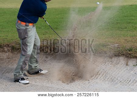 Thai Young Man Golf Player In Action Swing In Sand Pit During Practice Before Golf Tournament At Gol