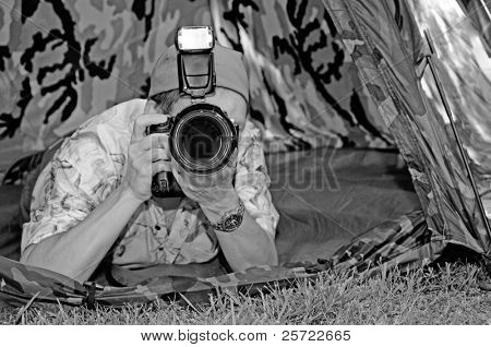 Nature photographer under cover in camouflage tent to get the shot