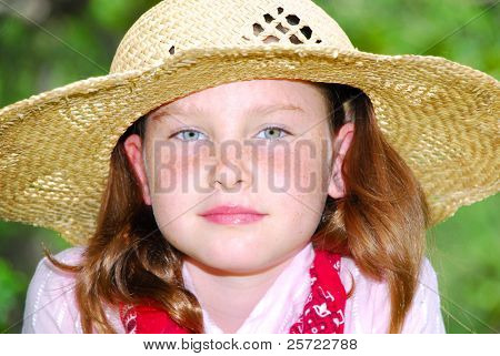 Young country girl in straw hat outdoors