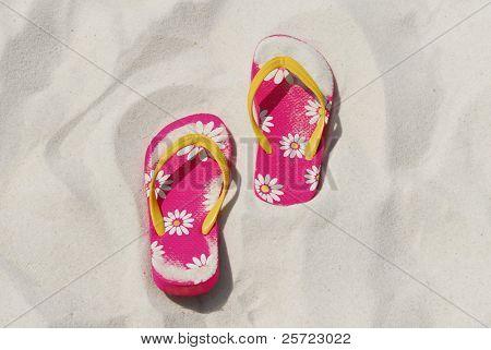 pretty pink flip flops stuck in soft white beach sand