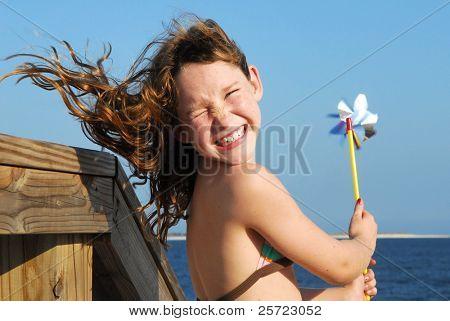 Young girl at windy beach having fun with pinwheel