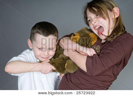 Young boy and girl fighting over toy bear