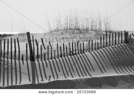Sand dune, fence and shadows on beach