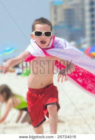 Young boy on beach pretending to be superhero poster