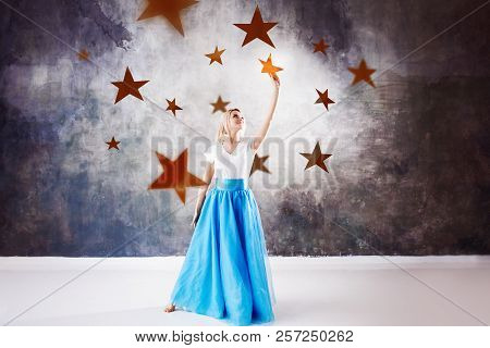 Young Beautiful Woman Took A Star From The Sky. Fantasy Concept, Reach For The Dream. A Lot Of Gold