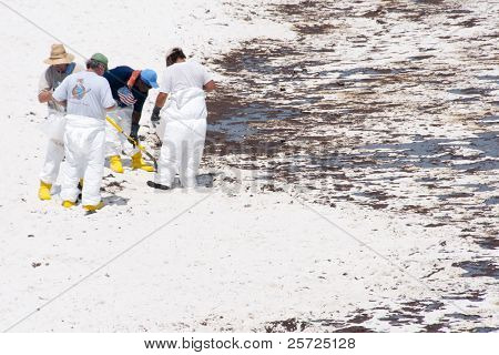 PENSACOLA BEACH - 23 JUNE:  Workers try to collect oil covered sand near the pier on June 23, 2010 in Pensacola Beach, FL.