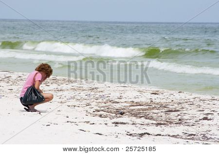 PENSACOLA BEACH - JUNE 23:  An unidentifed beachgoer crouches next to oil covered sand on June 23, 2010 in Pensacola Beach, FL.