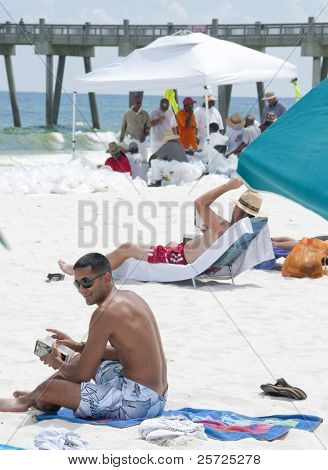 PENSACOLA BEACH - JUNE 23: Beachgoers rest on the beach on June 23, 2010 in Pensacola Beach, FL. BP oil workers are seen in the background.
