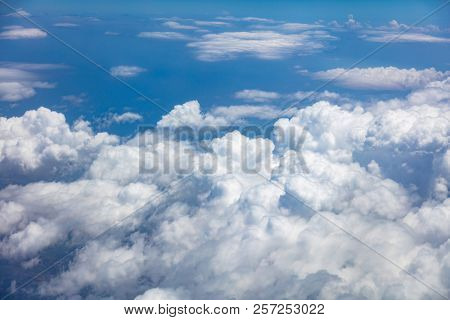 Blue sky, white fluffy clouds cover the earth background. Aerial photo from airplane's window.